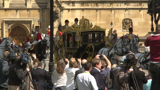 exterior wide shots crowd onlookers watching irish state coach carrying queen elizabeth on its way to houses of parliament on may 27 2015 in london... - the queen's speech state opening of uk parliament stock-videos und b-roll-filmmaterial