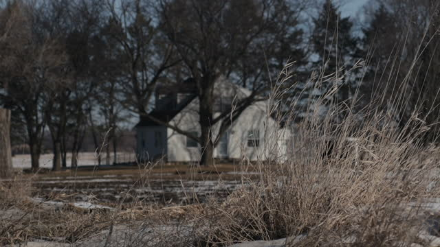 Exterior wide shots of a rural Iowan farm landscape with snowy fields a farm road and farm buildings on January 31st in Des Moines Iowa
