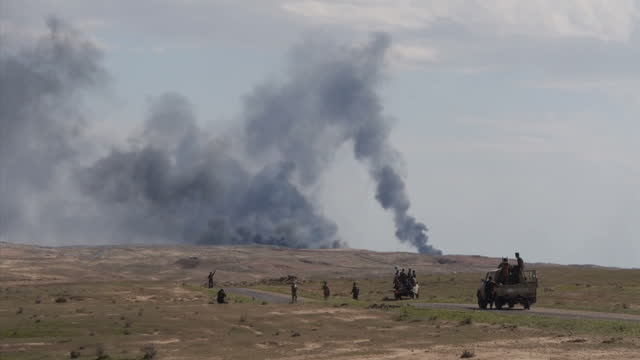exterior wide shots of black smoke from burning oil wells afetr is militants set ablaze the two oilfields of himrin and ajil northeast of tikrit on... - home guard britannica video stock e b–roll