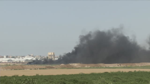 exterior wide shots of black smoke rising and demonstrators gathered at the israeli / gaza border during protests and clashed on 6th april 2018 in... - 2018 gaza border protests stock videos & royalty-free footage
