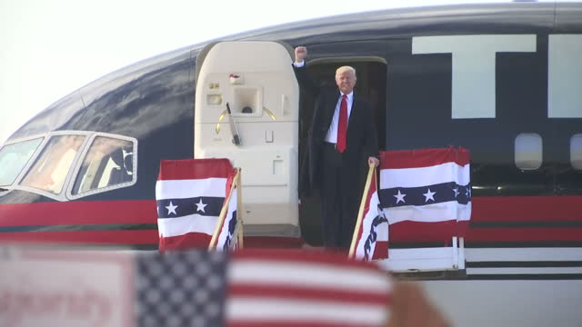 Exterior wide shots of Donald Trump arriving by plane and speaking to supporters waving posters and departing on his private jet on November 4 2016...