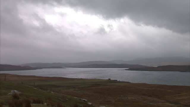 exterior wide shots of landscape and lochs in the outer hebridies with a cloudy, grey sky and the sun barely shining through on march 19, 2015 on the... - äußere hebriden stock-videos und b-roll-filmmaterial