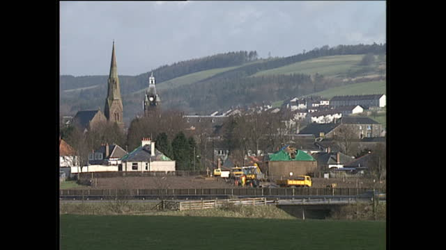 exterior wide shots of local landmarks and diggers at a site in the town of lockerbie approximately three months after the pan american flight 103 en... - lockerbie stock videos & royalty-free footage