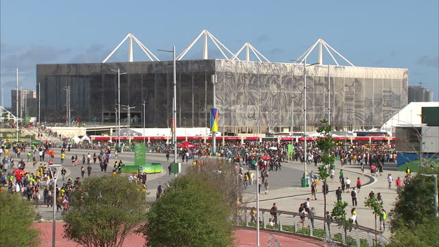 exterior wide shots of people walking through the olympic village wide shots of maracana stadium and the olympic rings on august 12 2016 in rio de... - 記号点の映像素材/bロール