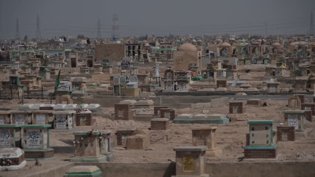stockvideo's en b-roll-footage met exterior wide shots of thousands of gravestones where shia muslim fighters are buried andrelatives visiting graves on march 21 2015 in najaf iraq - najaf