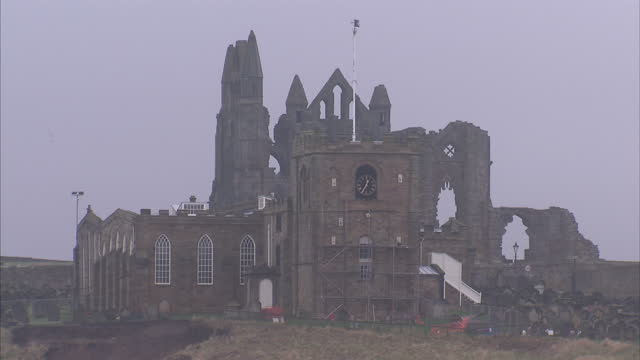 stockvideo's en b-roll-footage met exterior wide shots of whitby abbey ruins & the iconic whalebone arch on the west cliffs of whitby's eroding coastline. whitby abbey ruins &... - graaf dracula