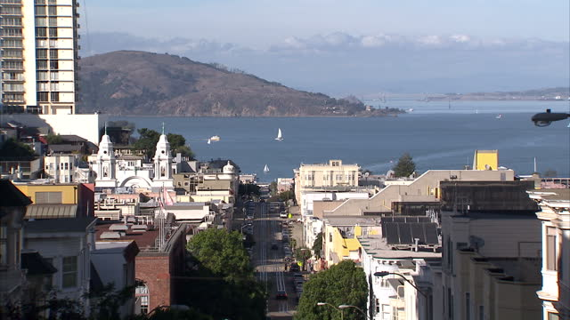 exterior wide shots san francisco hilly streets with san francisco bay in the background. exterior shots trams moving along city streets san... - san francisco bay stock videos & royalty-free footage