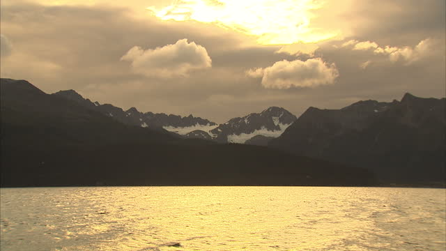 exterior wideshot landscapes of kenai fjords national park, showing sea water and glacier topped mountains at dawn, with an orange-toned hue. waves... - toned image stock videos & royalty-free footage