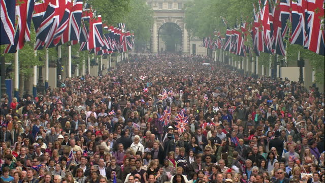 Exterior zoom into Buckingham Palace balcony Exterior shots crowds gathered by Buckingham Palace entrance along The Mall Exterior high shot crowds...