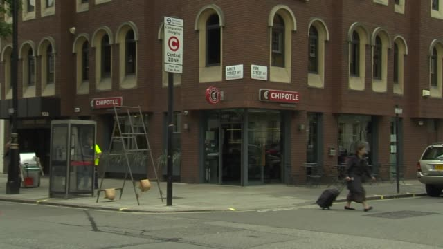 exteriors and signage of a chipotle restaurant in london england a double decker bus drives down baker street in london england revealing a chipotle... - メリルボーン点の映像素材/bロール