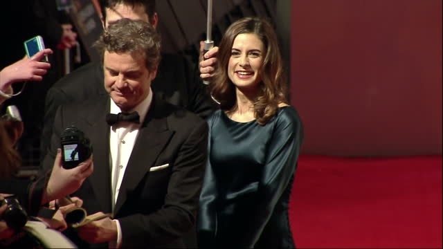stockvideo's en b-roll-footage met exteriors colin firth sign autographs on red carpet of the orange bafta awards with his wife livia alongside him colin firth and wife on bafta red... - bafta awards