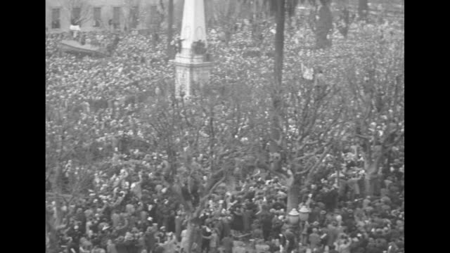 Exteriors National Bank of Argentina / large crowd with banner at rally in Plaza de Mayo / LS aerials crowd / crowd waving white handkerchiefs / men...