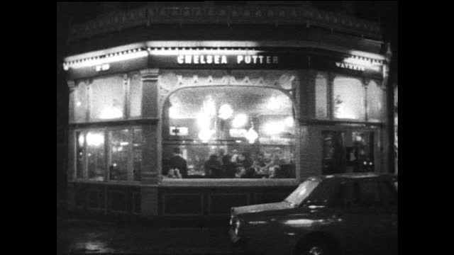 exteriors of brightly lit pub in chelsea looking in, london; 1967 - brightly lit stock videos & royalty-free footage