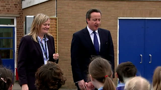 exteriors of british prime minister david cameron arriving on school playground, being mobbed by and talking to crowd of children, on february 09,... - 英国チェスター点の映像素材/bロール