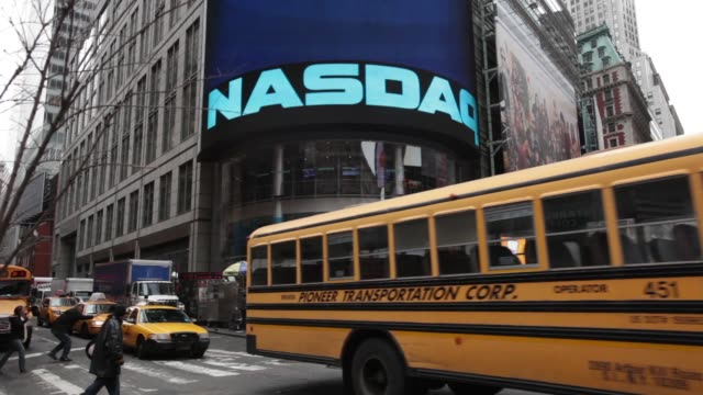 Exteriors of Nasdaq / taxis and cars driving by / digital ads for Reuters and Living Social / great colorful signage of entrance Nasdaq Close up on...