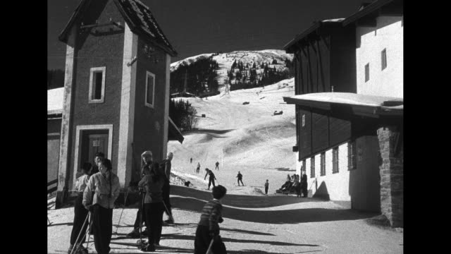 exteriors of roman catholic church / snow covered streets / people walking with sleds / people skiing down the mountain / aerials people skiing / - austria video stock e b–roll