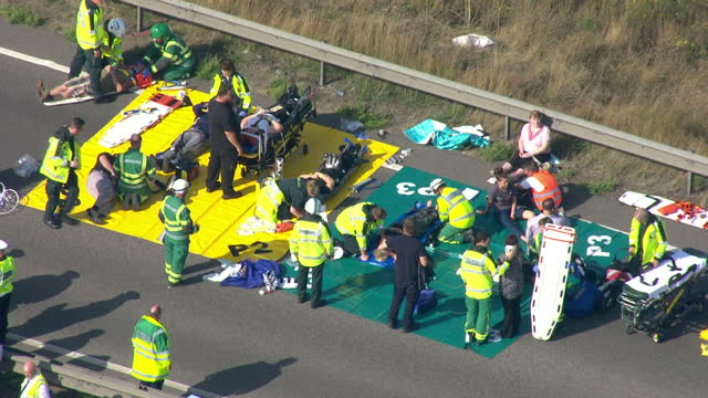 stockvideo's en b-roll-footage met exteriors paramedics in road near sheppey bridge treating injured motorists in field triage teams with other people waiting on opposite carriageway... - triage