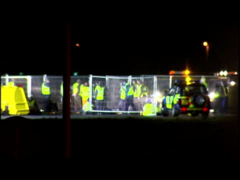 vídeos de stock, filmes e b-roll de exteriors protesters wearing hi vis jackets barricade themselves inside fences on runway. exteriors protesters on runway. exteriors men closing up... - 50 segundos ou mais