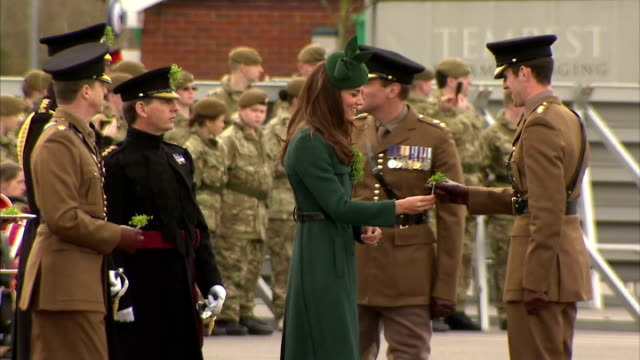 Exteriors shows Catherine Duchess of Cambridge giving out Shamrocks to various soldiers in turn soldiers in different uniforms on March 17 2014 in...