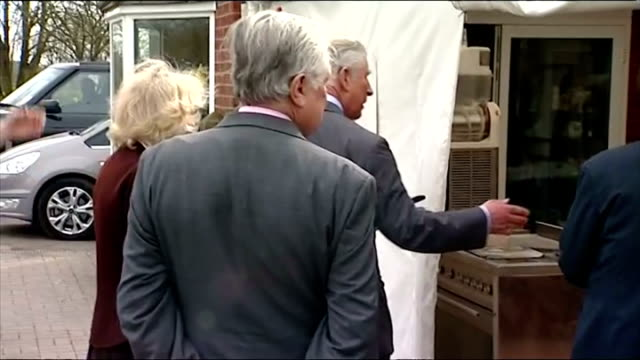 Exteriors shows Prince Charles and Camilla posing next to giant teapot wishing well Royal pair stand for photo op with local official press present...