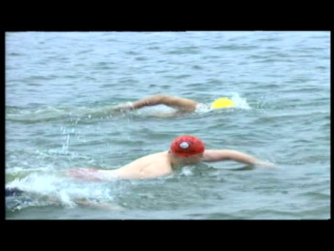 exteriors swimmers lined up by the serpentine banks preparing to dive in. exteriors swimmers diving in & starting to race. exteriors cyril wood... - running shorts stock videos & royalty-free footage