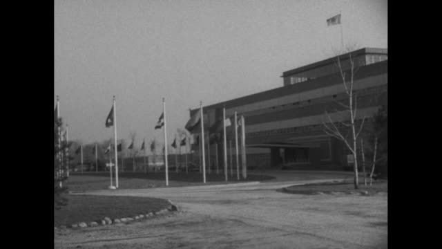 exteriors united nations temporary headquarters building at lake success / un nation flags waving in the breeze / cu several country flags - onu video stock e b–roll
