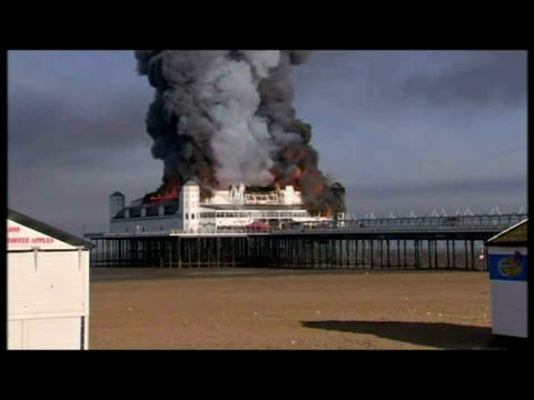 vidéos et rushes de exteriors var of weston super mare grand pier pavilion on fire, ablaze, smoke billowing into sky & firefighters at scene. - var