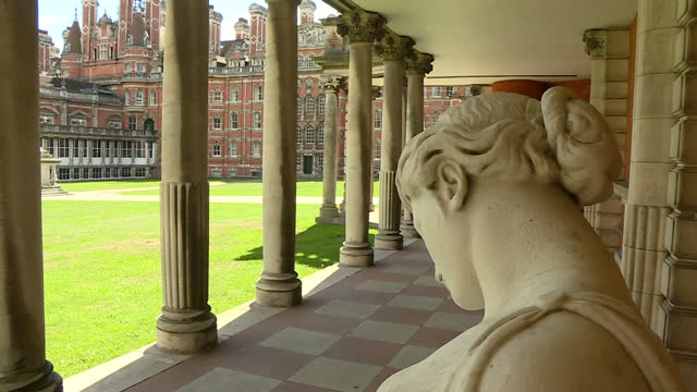 external low shots of royal holloway university building various of university courtyard by the founders building arty pan from statues to building... - サリー州点の映像素材/bロール