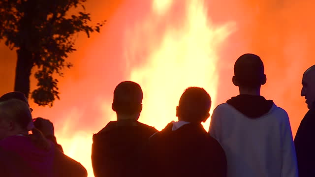 vídeos de stock, filmes e b-roll de external night shots of july 12th bonfire celebrations in belfast for battle of the boyne anniversary silhouettes of youths young people stand... - fogueira fogo ao ar livre