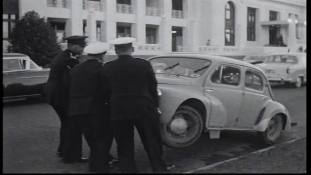 external of parliament house and cars arriving / blooper three policemen drag away small car they have lifted at the front morris minor / dignitaries... - ausrutscher stock-videos und b-roll-filmmaterial