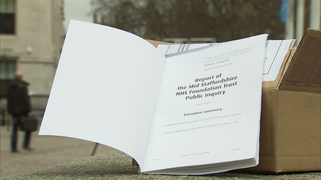 external set up shots woman reading 'report of the mid staffordshire nhs foundation trust public inquiry executive summary' stafford hospital report... - stafford england stock videos and b-roll footage