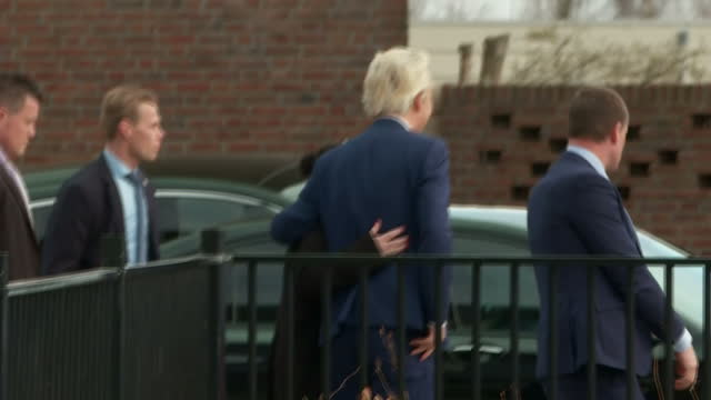 external shot geert wilders founder and leader of the party for freedom in netherlands walks up to journalists before voting in the netherlands... - オランダ点の映像素材/bロール