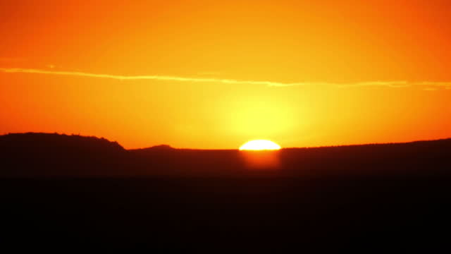 external shot of sunrise with bright warm orange sky land silhouette in laikipia kenya on sunday 6th august 2017 - one cloud sky stock videos & royalty-free footage