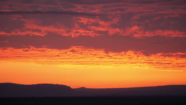 external shot of sunrise with bright warm orange yellow and pink sky land silhouette skyline rippled clouds in laikipia kenya on sunday 6th august... - kenia stock-videos und b-roll-filmmaterial