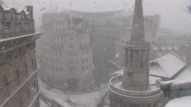 vídeos de stock, filmes e b-roll de external shot of the bbc's new broadcasting house during a heavy snow blizzard in london uk - chuva congelada