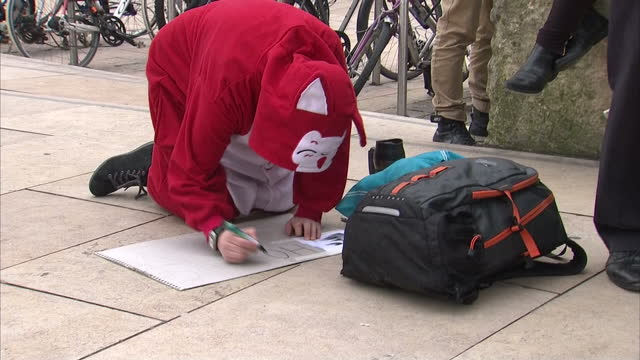external shots of a protester wearing a red cartoon cat 'onesie' kneeling on pavement writing placard during protest against welfare cuts in london... - placard stock videos & royalty-free footage
