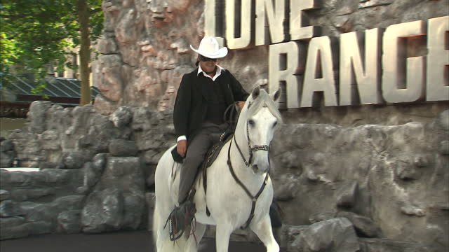 external shots of a stunt rider dressed as 'the lone ranger' riding a white horse performing stunts and riding up and down the cow print carpet at... - the lone ranger 2013 film stock videos and b-roll footage