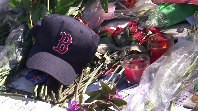 external shots of boston redsox baseball cap laid amongst other tributes near site of the boston marathon bombings street sign for boylston street on... - bombing stock videos & royalty-free footage
