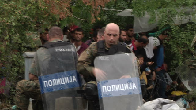 external shots of crowds of refugee migrants being contained by police behind barbed wire keeping them from crossing the hungary serbia border very... - 2015 stock-videos und b-roll-filmmaterial