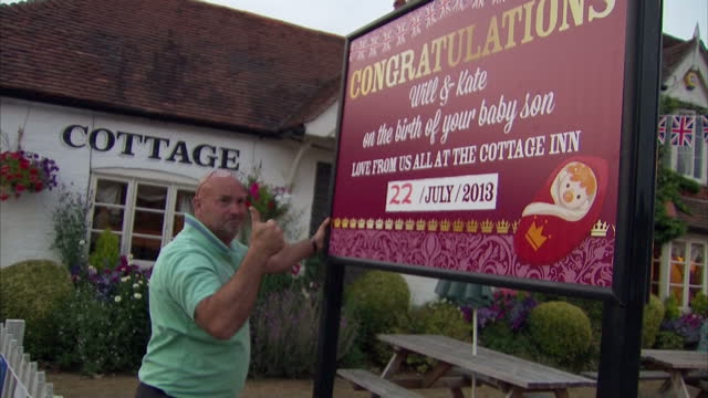 External shots of Gary Bush landlord of The Cottage Inn putting up sign congratulating the Duke and Duchess of Cambridge on the birth of their baby...