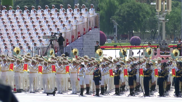 external shots of hundreds of military officials wearing smart white uniform with a yellow belt stood in neat rows stood behind the military parade... - military parade stock videos & royalty-free footage