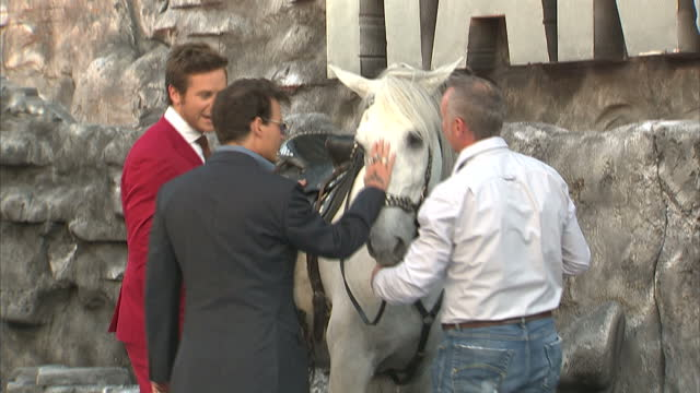 external shots of johnny depp armie hammer at 'the lone ranger' premiere johnny depp waves briefly to fans and speaks to armie hammer while patting... - the lone ranger 2013 film stock videos and b-roll footage