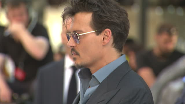 external shots of johnny depp posing for photographs on the black and white carpet at 'the lone ranger' film premiere in leicester square lone ranger... - the lone ranger 2013 film stock videos and b-roll footage