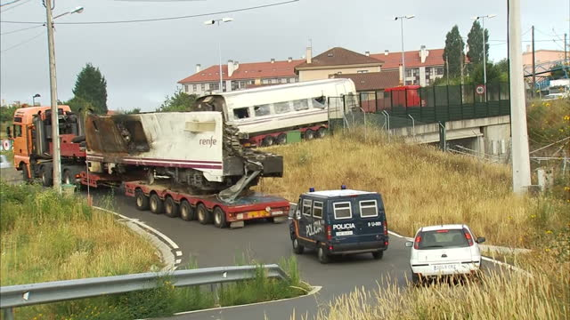external shots of lorries carrying away wreckage of train carriages that derailed near santiago de compostela clean up operation after train crash in... - 脱線点の映像素材/bロール