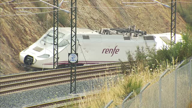 external shots of the engine car of the train that derailed outside santiago de compostela, with satellite trucks of media crews parked at top of... - 脱線点の映像素材/bロール
