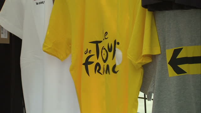 external shots of tour de france souvenir tshirts for sale and people browsing souvenirs for sale at a stall on the champs elysee tourists on the... - お土産点の映像素材/bロール