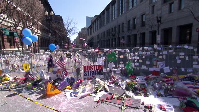 external shots of tributes to the victims of the boston bombings left near site of the bombings tributes include bouquets of flowers balloons... - bombing stock videos & royalty-free footage