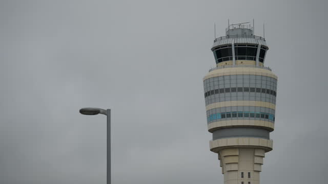 External shots outside HartsfieldJackson Atlanta International Airport on a grey skies cloudy day moody gloomy weather air traffic control tower and...