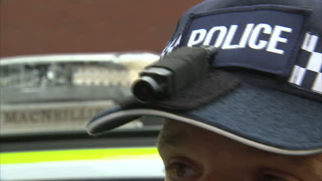 vídeos de stock e filmes b-roll de external shots police officer wearing body camera, pan to video & audio camera equipment on torso and camera attached to police cap in london,... - guarda roupa