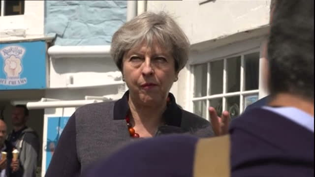 external shots prime minister theresa may campaigns in helston talks to workers smiling and laughing goes to local chip shop the fisherman's chippy... - cornovaglia video stock e b–roll